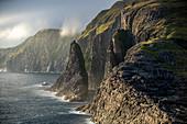 Steilküste im Westen der Insel Vágar mit dem Wasserfall Bøsdalafossur und der Felsnadel Geitaskoradrangur, Färöer Inseln, Dänemark