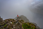 Hiker stands on a rocky slope at the summit of Klakkur in the fog, Klaksvík, Faroe Islands.