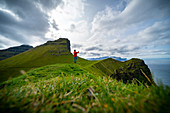 Hiker at Cape Kallur, northern tip of the island Kalsoy, Faroe Islands
