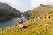 Woman looks out over the Saksun Lagoon, Streymoy Island in the Faroe Islands.