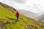 Photographer walks through the grassy mountain landscape between Saksun and Tjørnuvík, Streymoy, Faroe Islands