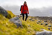 Fotografin wandert durch die grasbewachsene Berglandschaft zwischen Saksun und Tjørnuvík, Streymoy, Färöer Inseln