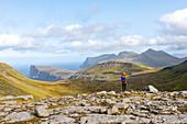 Fotografin wandert durch die grasbewachsene Berglandschaft zwischen Saksun und Tjørnuvík, Blick auf Tjørnuvík, Streymoy, Färöer Inseln