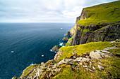 Steep coast in the Faroe Islands on a calm late summer day.