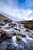 Stream and small waterfall on Sreymoy island with cloudy sky.