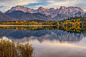 The Karwendel Mountains are reflected in the autumnal Barmsee, Krün, Bavaria, Germany