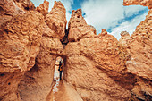 Woman running through rock gate in Bryce Canyon, Bryce Canyon National Park, Utah, USA, North America