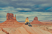 Woman sitting in front of Monument Valley, Arizona, Utah, USA, North America