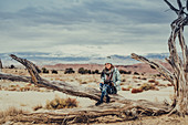 Woman sitting on parched trunk, desert landscape in Utah, USA, North America