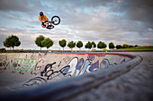 Man makes high jump with BMX in the Wiley Skatepark, Neu-Ulm, Bavaria, Germany, Europe