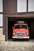 Vintage fire department automobile is parked in garage below a half-timbered house, Quedlinburg, Saxony-Anhalt, Germany, Europe