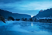View over the frozen Danube towards Werenwag Castle at dusk, Upper Danube Valley Nature Park near Sigmaringen in winter, Swabian Alb, Baden-Wuerttemberg, Germany, Europe