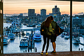 Young couple in front of viewing window of the Elbphilharmonie, view towards St. Pauli Landungsbruecken, Hamburg harbor, Sandtorhafen, Speicherstadt, Hafencity, Hamburg, Germany, Europe