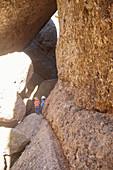 Children climb in the rocks of Pinnacles National Park, California, USA.