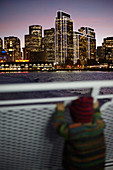 Child on a ferry in front of the sea of lights in San Francisco, California, USA.