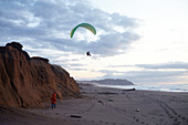 Paraglider pilot with young child at sunset on Point Reyes Beach, California, USA.