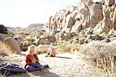 Children play on a rock against the backdrop of Jumbo Rocks in Joshua Tree Park, California, USA.
