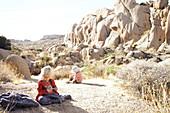 Kinder spielen auf einem Felsen vor der Kulisse der Jumbo Rocks im Joshua Tree Park, Kalifornien, USA