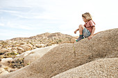 Young boy looks at the rocky landscape of Jumbo Rocks in Joshua Tree Park, California, USA.