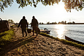 Danube Delta, an old couple carries shopping along the riverside path in the evening sun, Mila 23, Tulcea, Romania.