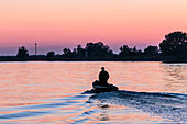 Boat in the Danube Delta. The man steers home, shifting his weight, hands in his pockets, with himself and the world in peace. Mila 23, Tulcea, Romania.