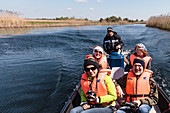 Tourists in life jackets on boat trip in Danube Delta in April, Mila 23, Tulcea, Romania.