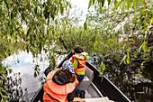 Tourists on a boat trip in the thicket of the Danube Delta in April, Mila 23, Tulcea, Romania.