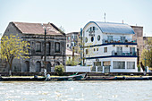 Danube Delta, old and new buildings on the banks of Sulina, Tulcea, Romania.