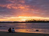 Couple at sunset on the beach with palm trees, Boipeba Island, Bahia, Brazil, South America