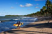 Young men with surfboards on the beach, Praia da Cueira, Boipeba Island, Bahia, Brazil, South America