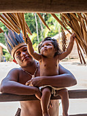 Man with toddler, indigenous people on the Amazon near Manaus, Nucleo Cultural Indigena Cipia, Amazon basin, Brazil, South America