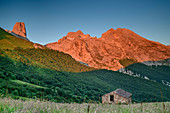 Alpine pasture buildings with Picu Urriellu in the morning light in the background, Naranjo de Bulnes, Refugio Terenosa, Picos de Europa, Picos de Europa National Park, Cantabrian Mountains, Asturias, Spain