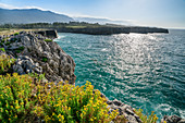 Sea on the steep coast of Playa de Guadamia, Bufones de Pria, mountains of the Picos de Europa in the background, Llames, Asturias, Spain