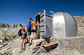 Three people hiking stand in front of hut Cabana Veronica, Cabana Veronica, Picos de Europa, Picos de Europa National Park, Cantabrian Mountains, Cantabria, Spain