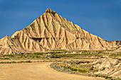 Ocher colored cone of erosion, Bardenas Reales, Bardenas Reales Natural Park, UNESCO Bardenas Reales Biosphere Reserve, Navarra, Spain