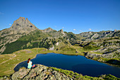 Woman while hiking sits on rock spur and looks at Lac Roumassot and Pic du Midi d´Ossau, Lac Roumassot, Pyrenees National Park, Pyrénées-Atlantiques, Pyrenees, France