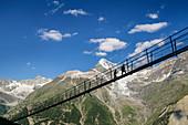 Two people walk over the Kuonen suspension bridge, longest suspension bridge in the world, Weißhorn in the background, Kuonen suspension bridge, Europaweg, Randa, Valais Alps, Valais, Switzerland
