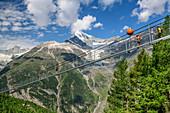 Several people walk over the Kuonen suspension bridge, the longest suspension bridge in the Alps, Weißhorn in the background, Kuonen suspension bridge, Europaweg, Randa, Valais Alps, Valais, Switzerland