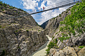 Woman while hiking stands on Aletsch suspension bridge, Aletsch suspension bridge, UNESCO World Natural Heritage Jungfrau-Aletsch, Bernese Alps, Switzerland