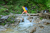 Woman hiking jumps over creek, Kraxenbachtal, Sonntagshorn, Chiemgau Alps, Chiemgau, Upper Bavaria, Bavaria, Germany