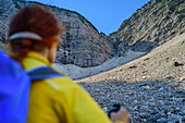 Woman hiking out of focus in the foreground looks at Schuttkar, Sonntagshorn, Chiemgau Alps, Chiemgau, Upper Bavaria, Bavaria, Germany