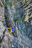 Woman mountaineering climbs through Schrofenwand, Sonntagshorn, Chiemgau Alps, Chiemgau, Upper Bavaria, Bavaria, Germany