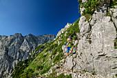 Woman mountaineering climbs via ferrata to Pyramidenspitze, Pyramidenspitz-Klettersteig, Pyramidenspitze, Kaiser Mountains, Tyrol, Austria