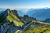 Woman hiking climbs up to Schöttelkarspitze, Schöttelkarspitze, Karwendel, Upper Bavaria, Bavaria, Germany