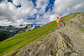 Man and woman hiking down from the Figerhorn, Grossglockner in clouds in the background, Figerhorn, Glockner Group, Hohe Tauern, Hohe Tauern National Park, East Tyrol, Austria