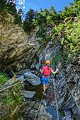 Woman commits rope bridge on Möllschlucht via ferrata, Möllschlucht, Glockner Group, Hohe Tauern, Hohe Tauern National Park, Carinthia, Austria