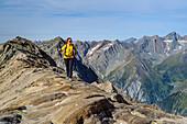 Woman hiking climbs over rocks to the Großer Muntanitz, Großer Muntanitz, Granatspitzgruppe, Hohe Tauern, Hohe Tauern National Park, East Tyrol, Austria
