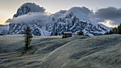Sunrise on the frosty Seiser Alm with a view of Langkofel and Plattkofel in South Tyrol, Italy