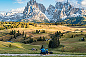 Father and son enjoy the sunset with a view of the snow-covered Langkofel and Plattkofel on the Alpe di Siusi in South Tyrol, Italy