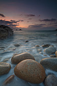 Boulders on Porth Nanven beach looking towards the Brisons at sunset Cot Valley near St Just Cornwall, UK